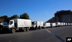 FILE - A convoy of humanitarian aid waits before making its way into the government-besieged rebel-held towns of Madaya, al-Zabadani and al-Moadhamiya in the Damascus countryside, as part of a U.N.-sponsored aid operation, in Damascus, Syria, Feb. 17, 2016.