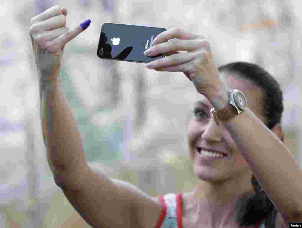 Una joven venezolana fotografía su dedo manchado con tinta como símbolo de que cumplió con su obligación electoral.