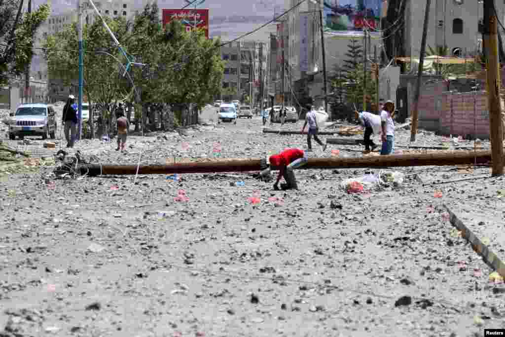 Seorang anak laki-laki menemukan selongsong senjata di jalanan yang terkena serangan udara 20 April. Serangan itu menghantam depot senjata militer di dekatnya, di Sana'a (21/4).(Reuters/Mohamed al-Sayaghi)