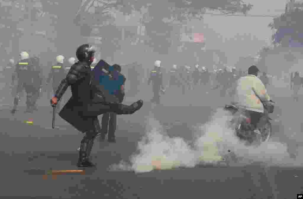 A riot police officer avoids a gas grenade as police fire gas grenades to disperse protesters in Phnom Penh, Jan. 27, 2014.