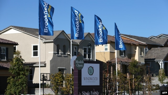 FILE - A sign advertising new homes is posted at a housing development in Dublin, California.