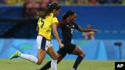 FILE - Colombia's Isabella Echeverri, left, and United States' Crystal Dunn go for the ball during a group G match of the women's Olympic football tournament between Colombia and United States at the Arena Amazonia stadium in Manaus, Brazil, Aug. 9, 2016.