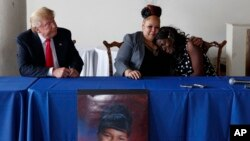 Republican presidential candidate Donald Trump, left, looks on as Shalga Hightower, center, hugs family spokesman Charmil Davis during a meeting, Sept. 2, 2016, in Philadelphia. Hightower's daughter, Iofemi Hightower, was murdered in a 2007 attack at a Ne