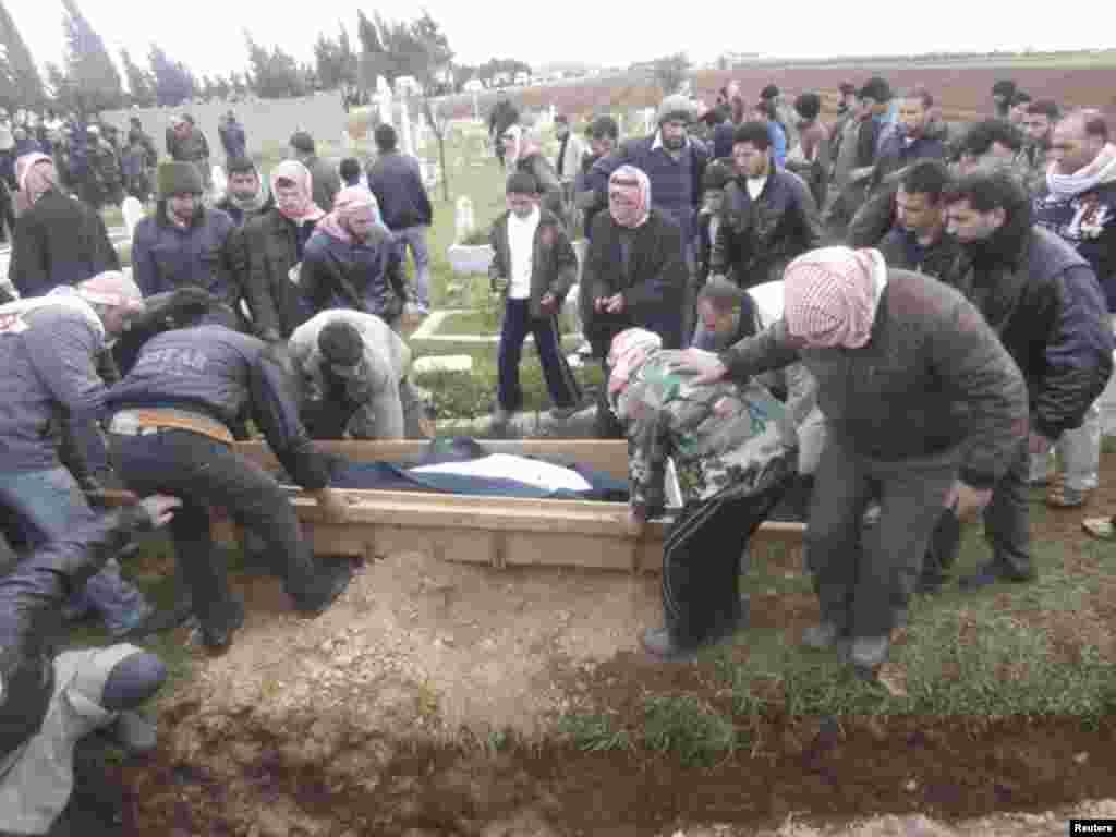 叙利亚自由军的战士和死者的亲属1月29日在霍姆斯附近掩埋活动人士称被忠于叙利亚总统阿萨德的部队杀害的人(沙姆新闻网)
