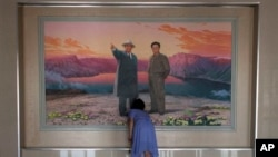 2013年6月21日一女子在朝鲜已故领导人金日成(左)和金正日(右)画像前安排花卉(美联社资料照片)