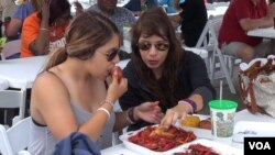 Two attendees share some tasty treats at the Brazoria County Crawfish Festival, south of Houston. (G. Flakus/VOA)