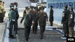 Para delegasi Korea Utara (tengah) saat memasuki perbatasan Korsel di Panmunjom sementara delegasi Korsel menunggu sebelum berlangsung pembicaraan Rabu (9/2).