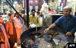 A Pakistani cook grills kebabs while customers look on at the Tory Kebab House in Namak Mandi in Peshawar, Dec. 13, 2018.