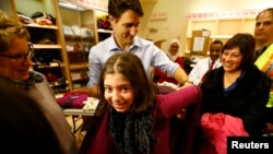 Canada's Prime Minister Justin Trudeau helps a young Syrian refugee try on a winter coat after she arrived with her family from Beirut at the Toronto Pearson International Airport in Mississauga, Ontario, Canada December 11, 2015. (REUTERS/Mark Blinch)