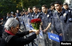 A demonstrator holds flowers before a police barricade during a commemoration for the victims of Saturday's bomb blasts in the Turkish capital, in Ankara, Turkey, October 11, 2015.