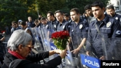 A demonstrator holds flowers before a police barricade during a commemoration for the victims of Saturday's bomb blasts in the Turkish capital, in Ankara, Turkey, Oct. 11, 2015.
