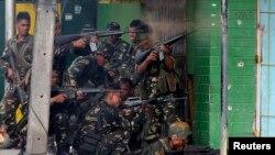 Tentara pemerintah menembakkan senjata-senjata mereka pada pemberontak Muslim dari Front Pembebasan Nasional Moro (MNLF) dalam pertempuran di kota Zamboanga, selatan Filipina (12/9). (Reuters/Erik De Castro)