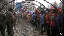 Cambodian garment workers, right, are blocked by barbed wire set up by police near the Council of Ministers building during a rally in Phnom Penh, Cambodia, Monday, Dec. 30, 2013. The workers are demanding a raise in their monthly salary from US $160 to $80. (AP Photo/Heng Sinith)