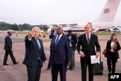 Ugandan Minister of Foreign Affairs Sam Kahamba Kutesa (C) welcomes British Foreign Secretary Boris Johnson (L), next to British High Commissioner to Uganda Peter West (R), upon his arrival at the Entebbe International Airport on March 15, 2017.