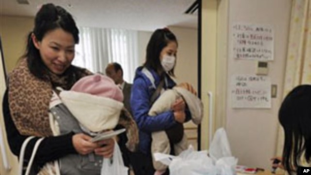 Mothers receive bottled water at a healthcare center in Tokyo  as the Tokyo Metropolitan Government starts to distribute three small bottles of water each to an estimated 80,000 families with babies of 12 months or younger. March 24, 2011