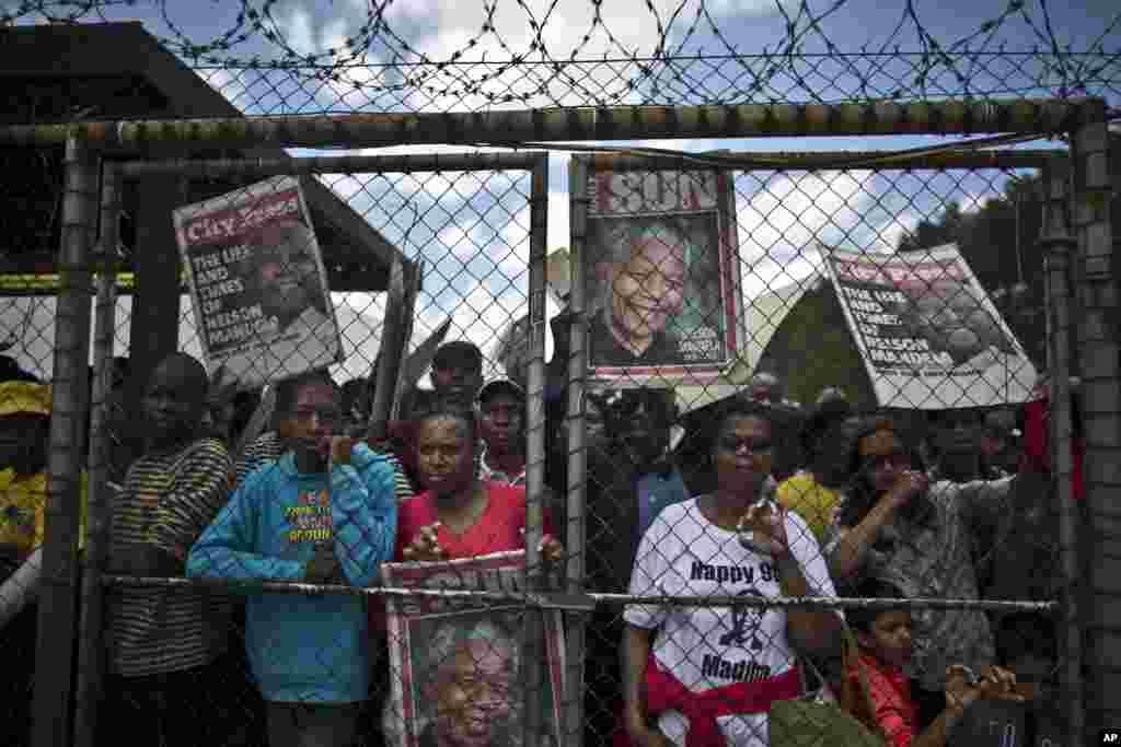 Pessoas alinham-se depois de esperarem horas para apanhar o autocarro até ao Union Building onde a urna de Nelson Mandela estará durante três dias, em Pretoria, Dez. 11, 2013.