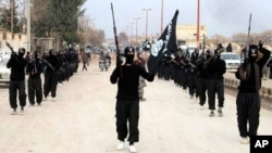 FILE - This undated file image posted on a militant website shows fighters from the al-Qaida linked Islamic State of Iraq and the Levant (ISIL) marching in Raqqa, Syria.