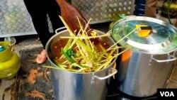 Proses pengolahan empon-empon dan berbagai rempah-rempah untuk minuman Pokak di dapur umum Pemkot Surabaya (foto Petrus Riski-VOA).