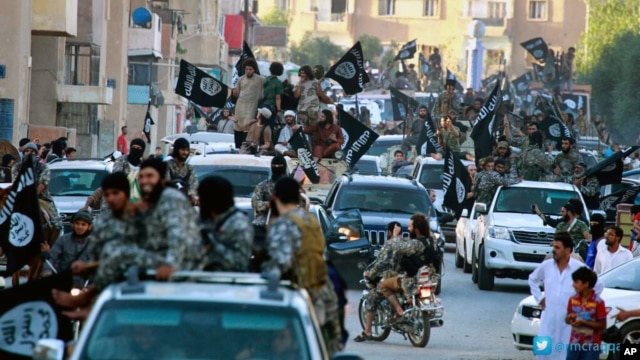 FILE - Fighters from the Islamic State group parade in Raqqa, north Syria, earlier this year.
