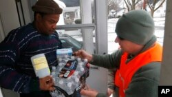 FILE - Michigan National Guard specialist Joe Weaver, right, delivers clean water supplies to Louis Singleton and other residents of Flint, Jan. 21, 2016.