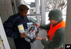 FILE - Louis Singleton receives water filters, bottled water and a test kit from Michigan National Guard Specialist Joe Weaver as clean water supplies are distributed to residents, Jan. 21, 2016 in Flint, Mich.