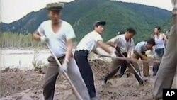 Para pekerja membangun tanggul dalam upaya mencegah banjir di Korea Utara, Senin (12/9).