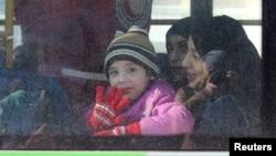 Un niño y su familia parten de Alepo, Siria, al comenzar la evacuación de civiles.