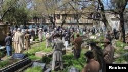 Ilustrasi. Orang-orang berdiri dan menjaga jarak yang aman ketika mereka menghadiri pemakaman orang yang meninggal karena corona di pemakaman di Abbottabad, Pakistan, 29 Maret 2020. (Foto: Reuters/Sultan Mehmood)