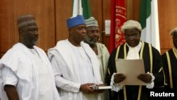Bukola Saraki (2nd L) takes the oath of office as the senate president of the 8th Nigeria Assembly in Abuja, Nigeria June 9, 2015. Also pictured are Senator Dino Melaye (L), Senator Sani Yerima and National Assembly Clerk Salisu Maikasuwa (R). REUTERS/Af