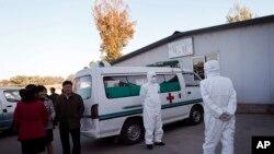 지난달 27일 평양 순안 공항에서 안전복장을 착용한 의료진이 구급차 옆에서 대기하고 있다. (자료사진)