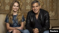 """Cast members George Clooney and Britt Robertson pose for a portrait while promoting their upcoming movie """"Tomorrowland"""" in Beverly Hills, California, May 8, 2015."""