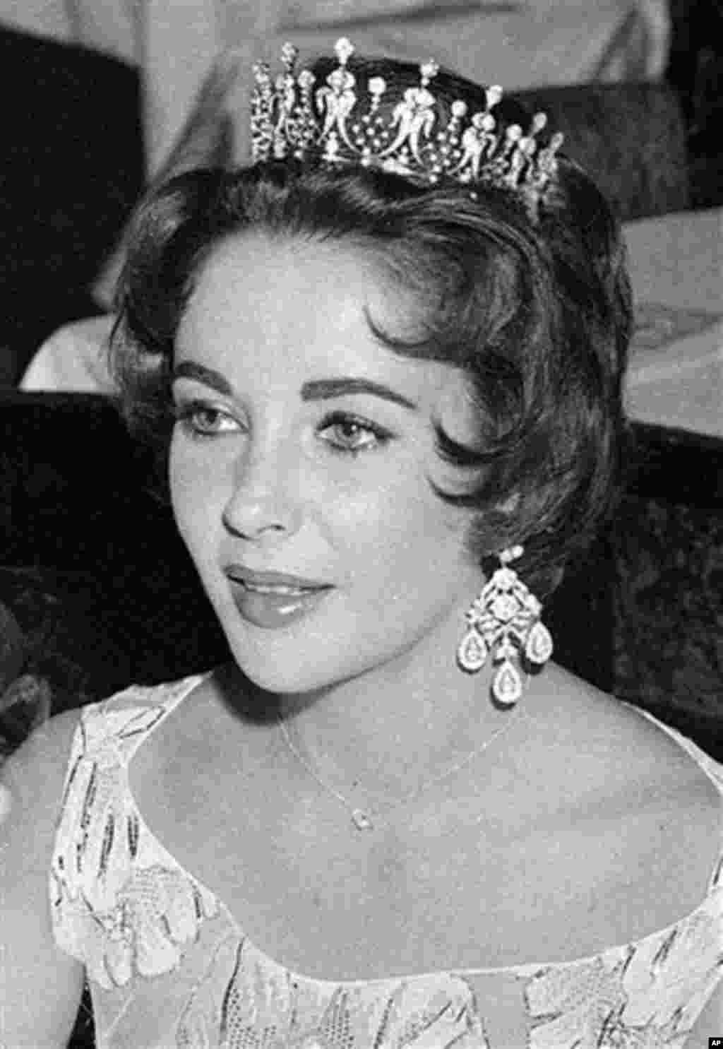 Actress Elizabeth Taylor, decked out in a glittering tiara and large drop earrings, is seen at the St. Valentine's Ball given by the American community in Paris, February 14, 1958 - AP