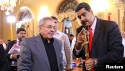 FILE - Venezuela's President Nicolas Maduro, right, shows a sword of Venezuelan national hero Simon Bolivar to Cuba's President Raul Castro in Caracas, Venezuela, March 5, 2017.
