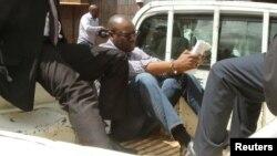 Le pasteur Evan Mawarire lit sa bible, escorté par des inspecteurs de la police à l'arrière d'une camionnette au tribunal d'Harare, Zimbabwe, 3 février 2017.