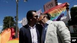 Javier Benalcázar, izquierda, y su pareja Efraín Soria se besan a su llegada a la Corte Constitucional para escuchar la decisión final del organismo sobre el matrimonio igualitario en Quito, Ecuador, el martes 4 de junio de 2019. (AP Foto/Dolores Ochoa).