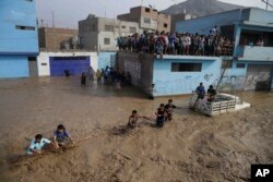 A group of people, stranded in flood waters, hold onto a rope as they walk to safety in Lima, Peru, March 17, 2017. Intense rains and mudslides recently have wrought havoc around the Andean nation and caught residents in Lima, a desert city of 10 million