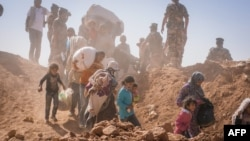 FILE - This handout picture taken on Jan. 22, 2014, and released on Aug. 29, 2014, shows Syrian refugees who stream across the border into Jordan at a remote border point in the east.