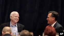 Mantan Gubernur Massachusetts Mitt Romney bercanda dengan Senator John McCain dalam sebuah acara di Scottsdale, Jumat (20/4).