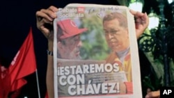 "People hold a newspaper showing images of Cuba's Fidel Castro, left, and Venezuela's President Hugo Chavez next to the headline in Spanish ""We will be with Chavez!"" during a gathering in support of Chavez's health in Caracas, Venezuela, late Friday July 1"