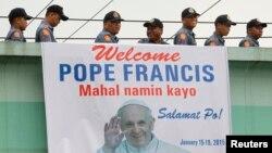 Polisi melewati spanduk bergambar Paus Fransiskus di Manila, Filipina (15/1).
