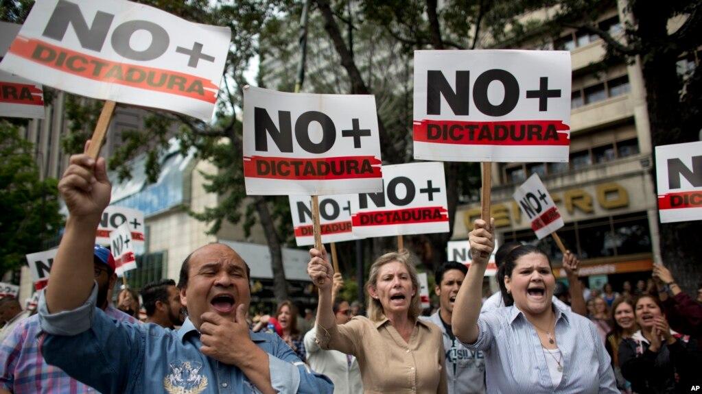 """Người biểu tình chống tổng thống Maduro mang biểu ngữ có dòng chữ """"Chấm dứt độc tài"""", Caracas, 30 tháng Giêng."""
