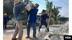 Các lão nông đang tham gia xây cầu. Hình: Trích xuất từ website báo Tuổi Trẻ/Hải Triều.