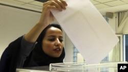 A Saudi woman casts her ballot at a polling center during municipal elections in Riyadh, Saudi Arabia, Dec. 12, 2015.