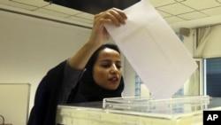 Seorang perempuan Saudi memberikan suaranya dalam pemilihan kepala daerah di Riyadh. Untuk pertama kalinya pada Desember 2015, perempuan di Arab Saudi diperbolehkan memilih dan menjadi peserta pemilihan umum. (AP/Aya Batrawy)