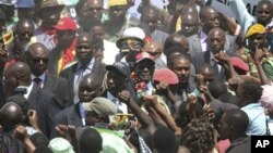 Zimbabwean President Robert Mugabe, center, greets the crowd as he arrives for his 88th birthday celebrations in Mutare, Zimbabwe Saturday, Feb. 25, 2012.