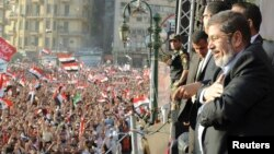 FILE - Egypt's Islamist President-elect Mohamed Mursi looks at the crowd awaiting his speech in Cairo's Tahrir Square, June 29, 2012.