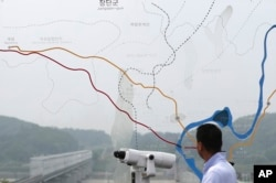 FILE - A man watches the north side through the glass showing a map of the border area between North and South Koreas at the Imjingak Pavilion near the Panmunjom, which has separated the two Koreas since the Korean War, in Paju, South Korea, July 6, 2017.