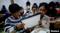 (Ảnh tư liệu) - Sinh viên Trung Quốc cầm một màng lọc HEPA để chuẩn bị lắp lên một chiếc quạt tại một buổi hội thảo ở Bắc Kinh dạy cách làm máy lọc DIY.