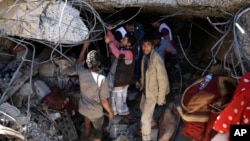 FILE - People search for survivors in the rubble of a house destroyed by Saudi-led airstrikes that killed a TV director, his wife and three children in Sanaa, Yemen, Feb. 10, 2016.