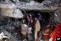 FILE - People search for survivors under the rubble of a house destroyed by Saudi-led airstrikes that killed a TV director, his wife, and three children in Sanaa, Yemen, Wednesday, Feb. 10, 2016.